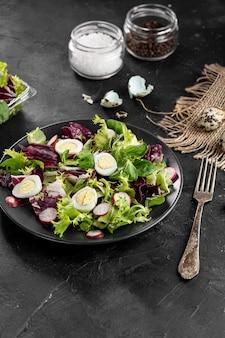 Disposizione dell'insalata dell'angolo alto sulla tavola scura