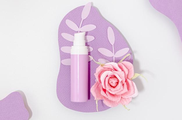 Disposizione della bottiglia di trucco viola con rosa rosa