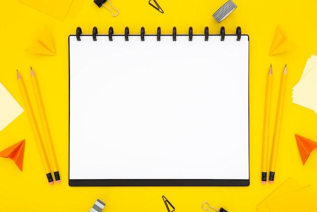Disposizione della cancelleria di vista superiore su fondo giallo con il taccuino vuoto
