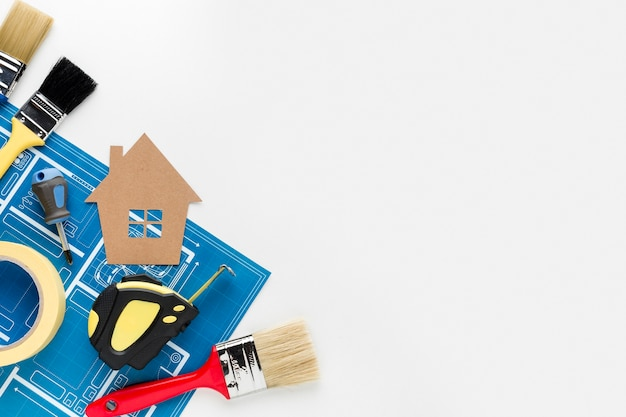 Disposizione della casa del cartone e strumenti di riparazione con lo spazio della copia