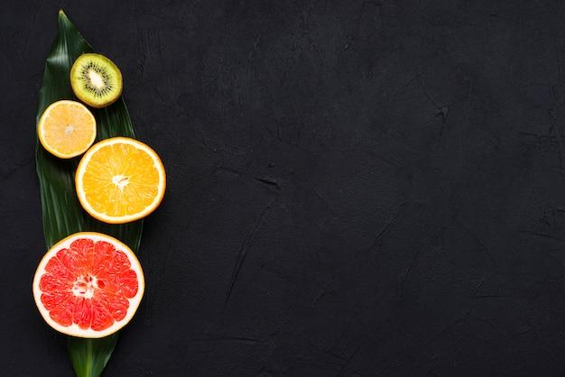 Disposizione della metà dei frutti tropicali su foglia di banana su sfondo nero