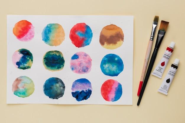 Disposizione della pittura astratta del cerchio; pennello e tubo di vernice