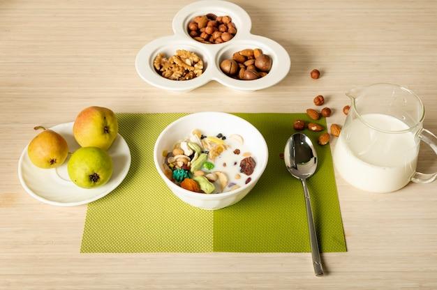 Disposizione della prima colazione di frutta, noci e cereali su sfondo chiaro