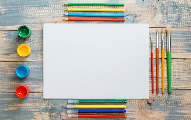 Disposizione delle attrezzature pittoriche colorate e foglio bianco sul fondale in legno