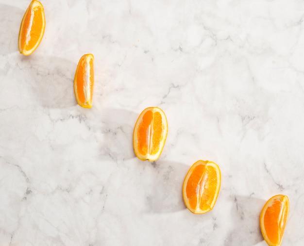 Disposizione delle fette d'arancia su fondo di marmo