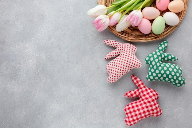Disposizione delle uova di pasqua multicolori e decorazioni a forma di coniglietto