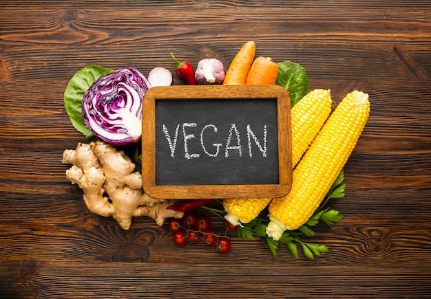 Disposizione delle verdure vista dall'alto con scritte vegan sulla lavagna