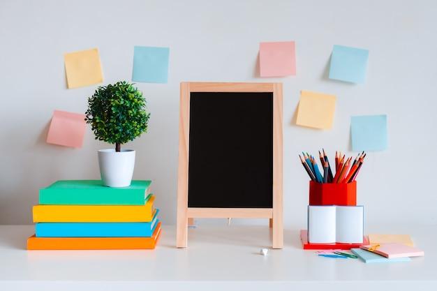 Disposizione desktop creativa dello studente con elementi decorativi colorati, matite colorate e libri luminosi su uno sfondo di muro bianco.