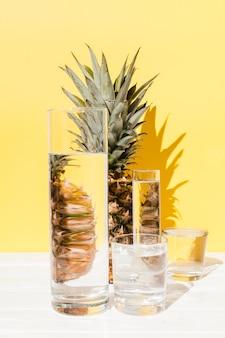 Disposizione di ananas e bicchieri