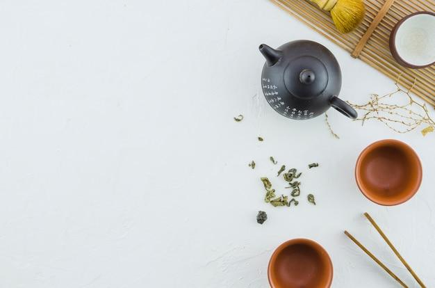 Disposizione di cerimonia di tè asiatica tradizionale su priorità bassa bianca