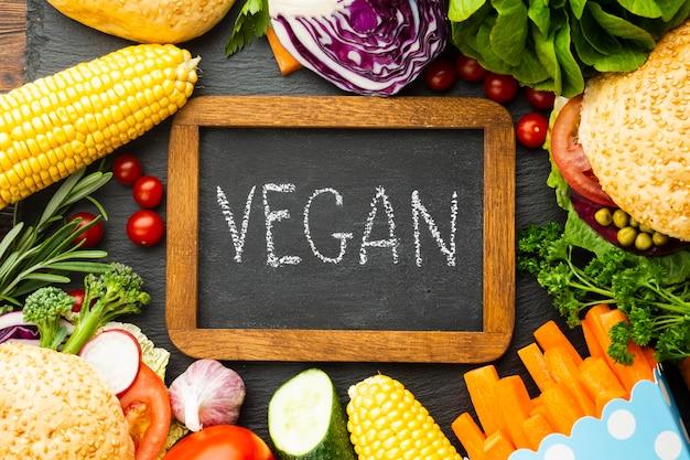Disposizione di cibo sano con scritte vegan sulla lavagna