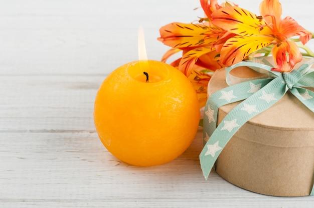 Disposizione di fiori di giglio arancione e candela, confezione regalo