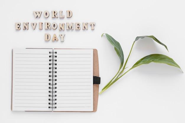 Disposizione di giornata mondiale dell'ambiente con il taccuino vuoto