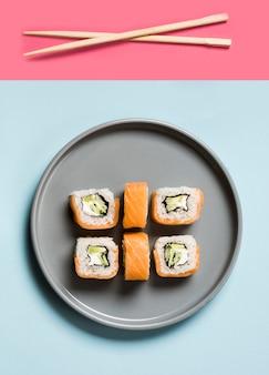 Disposizione di involtini di sushi con bacchette e salsa di soia