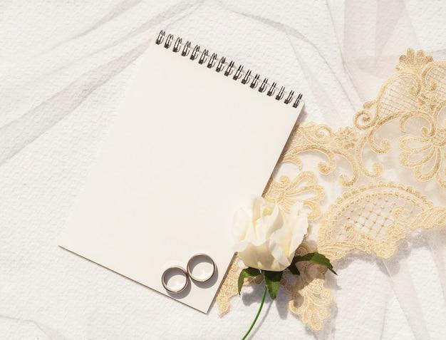 Disposizione di matrimonio femminile piatta con blocco note vuoto