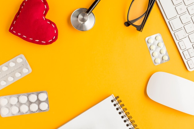 Disposizione di medicinali confezionati in blister; a forma di cuore cucito; blocco note a spirale; tastiera senza fili; topo; occhiali; stetoscopio su sfondo giallo