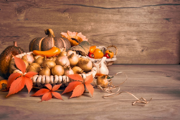 Disposizione di natura morta di autunno all'interno sulla tavola di legno invecchiata. composizione autunnale del ringraziamento con cesto di cipolle, zucche decorative, foglie di autunno e piccoli peperoni gialli