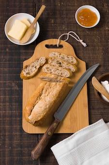 Disposizione di pane e ingredienti su tavola di legno