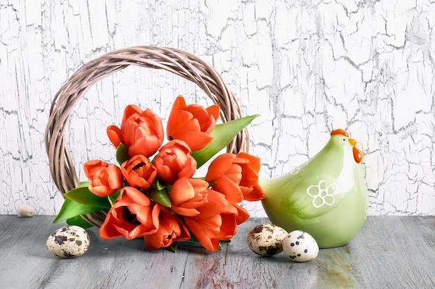 Disposizione di pasqua con ghirlanda di legno, tulipani rossi, gallina in ceramica e uova di quaglia