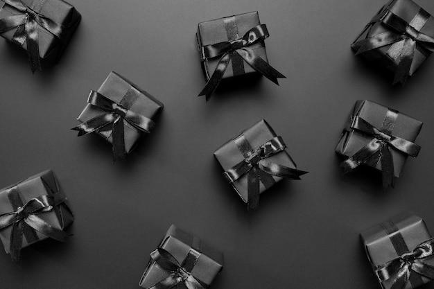 Disposizione di regali neri su sfondo nero