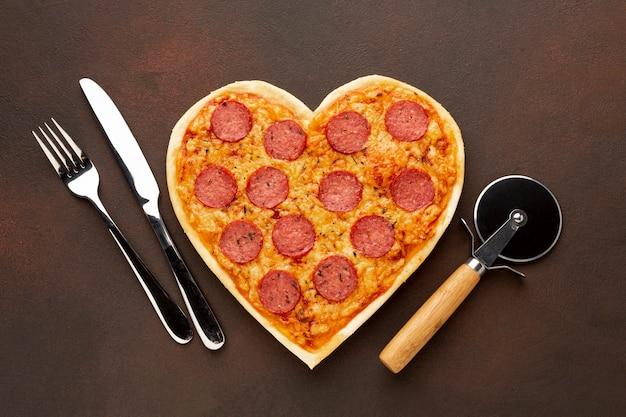 Disposizione di san valentino con pizza e stoviglie a forma di cuore