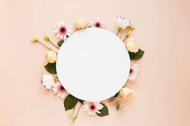 Disposizione di vari fiori primaverili e pezzo di carta rotondo vuoto
