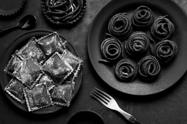 Disposizione di vista superiore di alimento delizioso nero sul piatto e sulla tavola scuri