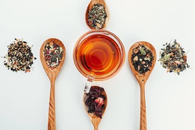 Disposizione fatta della tazza di tè nero e foglie su bianco