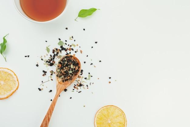 Disposizione fatta della tazza di tè nero e foglie su un bianco. vista dall'alto