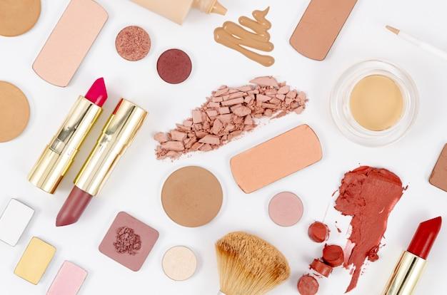 Disposizione femminile dei cosmetici su fondo bianco