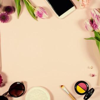 Disposizione femminile di bellezza creativa di fiori e cosmetici