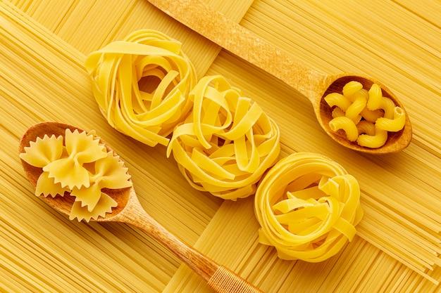 Disposizione geometrica di spaghetti crudi con tagliatelle farfalle e cellentani