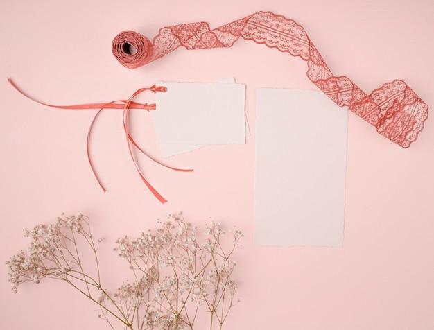 Disposizione graziosa di vista superiore per gli inviti di nozze su fondo rosa