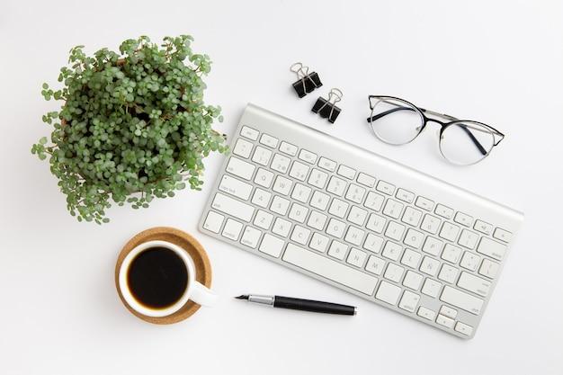 Disposizione moderna del posto di lavoro di vista superiore su fondo bianco