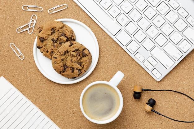Disposizione moderna sul posto di lavoro con piatto di biscotti