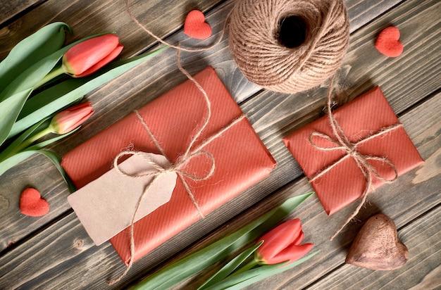 Disposizione pasquale: tulipani rossi, regali incartati, cordoncino e cuori decorativi su tabke in legno, disposizione piatta