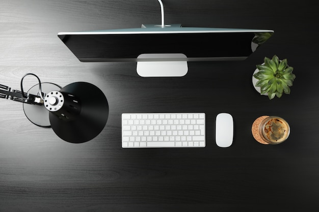 Disposizione piana con il computer, la pianta e il bicchiere di caffè sulla tavola di legno nera, vista superiore
