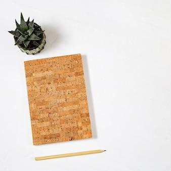 Disposizione piana con il quaderno di moda per la scrittura e il disegno, matita di legno con grafite, pianta succulenta verde sul ripiano del tavolo con lo spazio della copia. vista dall'alto