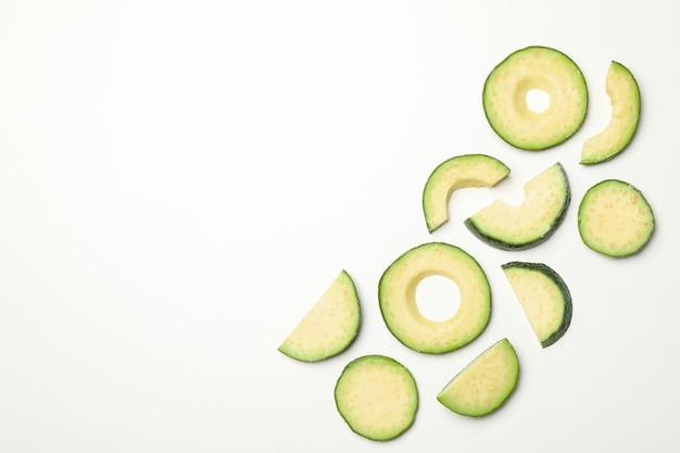 Disposizione piana con le fette di avocado su fondo bianco, vista superiore