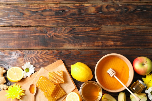 Disposizione piana con miele, fiori e frutti su fondo di legno, spazio per testo