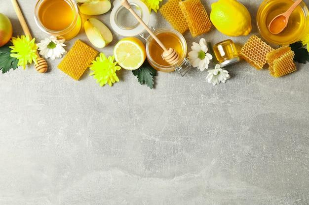 Disposizione piana con miele, fiori e frutti su fondo grigio, spazio della copia