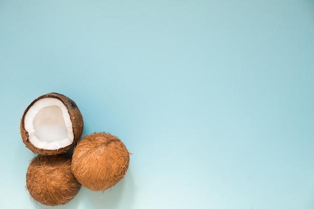 Disposizione piana con noci di cocco mature sul blu