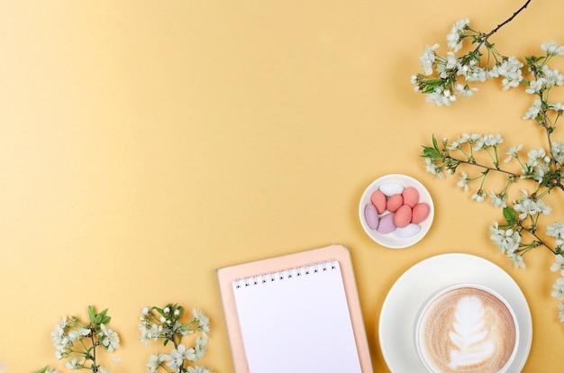 Disposizione piana creativa degli oggetti dello scrittorio, del blocco note e di stile di vita dell'area di lavoro su fondo giallo