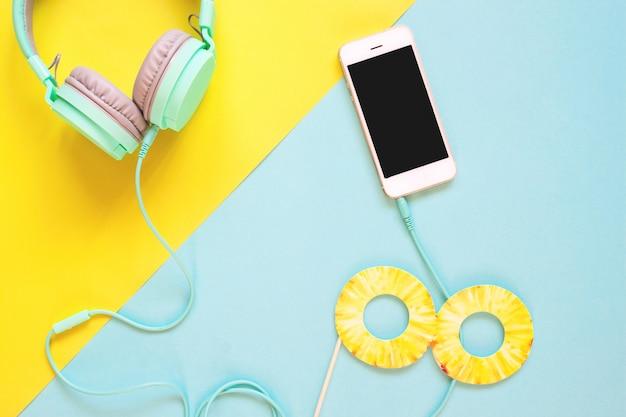 Disposizione piana creativa del concetto di estate con lo smart phone e le cuffie sul fondo di colore