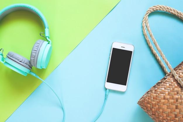 Disposizione piana creativa della raccolta di estate con lo smart phone sul fondo di colore