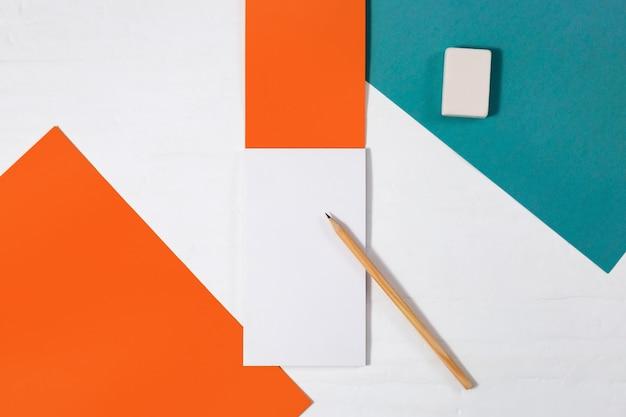Disposizione piana creativa della scrivania dello spazio di lavoro per persona creativa. mock up taccuino aperto, matita di legno e gomma