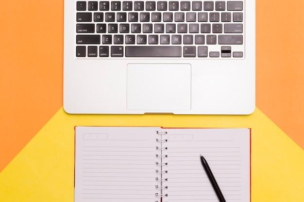 Disposizione piana creativa dello scrittorio del posto di lavoro con fondo arancio e giallo