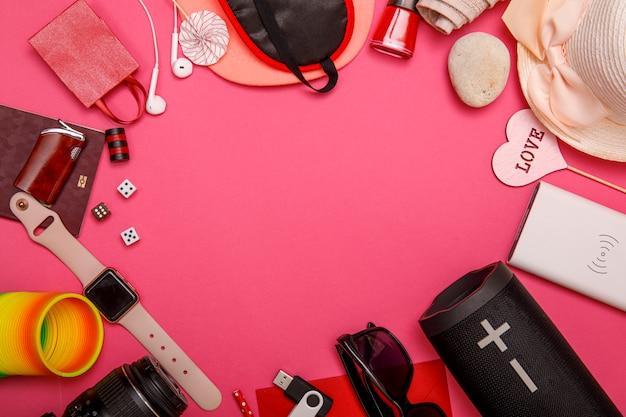 Disposizione piana degli accessori di viaggio con il passaporto, la vecchia macchina fotografica, gli occhiali da sole, il powerbank, l'altoparlante del bluetooth e lo smalto su fondo variopinto con lo spazio della copia, vista superiore. tutto ciò che serve per confortare il viaggio.