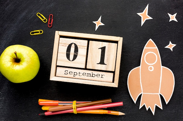 Disposizione piana degli elementi essenziali della scuola con calendario e mela