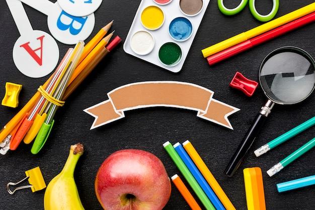 Disposizione piana degli elementi essenziali della scuola con frutta e matite
